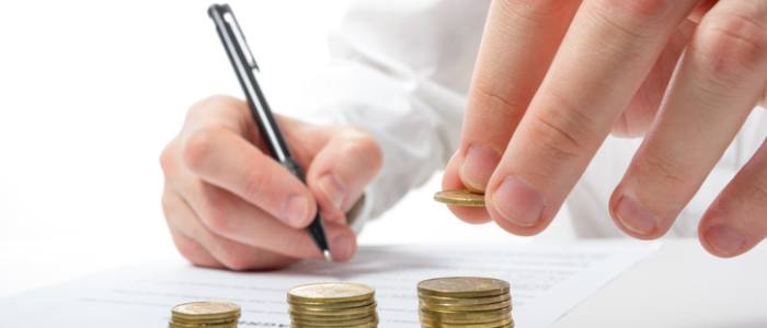 Business concept. Businessman's hand counting money on calculator and signing documents at office workplace, office work. Stack of coins. Financial Accounting - money and calculator. Businessman counting losses and profit working with statistics, analyzing financial the results.